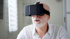 Good-looking handsome senior man in white using VR 360 glasses at home. Active modern elderly people. Concept. Seeing something unusual and exciting, learning stock video footage