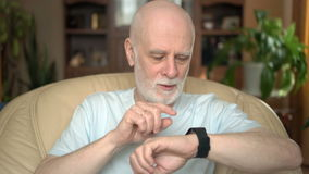Good-looking handsome smiling senior man sitting on chair at home. Using smartwatch, browsing, reading stock video