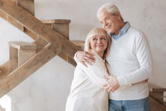 Good looking happy couple standing together. Absolutely happy. Good looking cheerful happy couple standing together and smiling while hugging each other Stock Photos