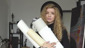Artist with sketches. Good-looking happy girl with lovely curly hair holding a few huge sketches, a day in life of artist, indoor portrait shot stock footage