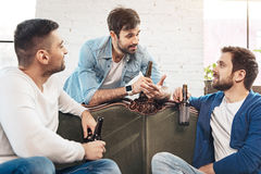 Good looking joyful friends having a conversation. Pleasant interaction. Good looking nice joyful friends having a conversation and having beer while resting at Stock Photo