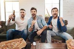 Good looking joyful men cheering for their football team royalty free stock photos