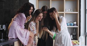 Good looking ladies with attractive smile have a bachelorette party at home in pajamas they smiling large and looking. Through a smartphone in amazing loft stock video