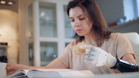 Good-looking lady with a bionic hand is reading and eating a cookie. 4K stock footage