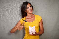 Good-looking lady breaking piggy bank with hammer Stock Image