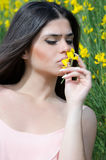 Good looking lady smelling yellow flower Stock Images