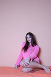 Good looking lady wearing knitting pink blouse against house wall Stock Photography