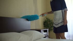 Good looking maid wiping dust on bed furniture, high quality room cleaning