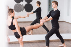 Good looking male dancer holding the leg of his partner stock images