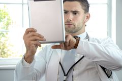 Good looking male doctor, gp, with stethoscope and tablet stock photo