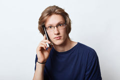 Good-looking male enterpreneur, wearing elegant spectacles, making business call to his partner, asking for meeting with him, havi. Ng conversation with serious Royalty Free Stock Photos