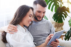 Good-looking male and female sitting on sofa and surfing in tabl. Close-up of good-looking male and female sitting on sofa and surfing in tablet in sunny room Stock Photos