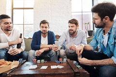 Good looking male friends playing poker. Game for true men. Good looking positive male friends sitting together around the table and playing poker while spending Royalty Free Stock Photography