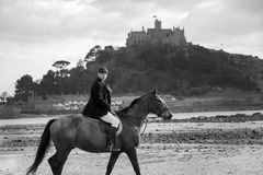 Good Looking  Male Horse Rider riding horse on beach in traditional riding clothing with St Michael`s Mount in background. Handsome, British man, male horse Stock Photos
