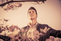 Good looking male model at couuntryside, among. Flowers, enjoying nature with eyes closed Royalty Free Stock Photo