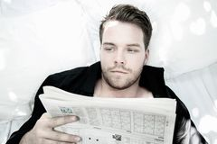 Handsome man with blue eyes lies in bed with white sheets reading paper Royalty Free Stock Images