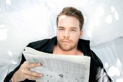 Handsome man with blue eyes lies in bed with white sheets reading paper Stock Photo