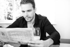 Good looking man at breakfast table, drinking and reading newspaper Stock Images