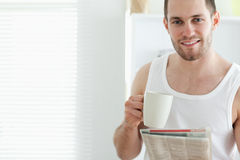 Good looking man drinking tea while reading the news Stock Images