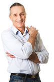 Good looking man with folded arms. Smiling mature man with folded arms Stock Image
