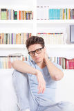 Good looking man with glasses with neck pain. Posing sitting in front of book shelf Royalty Free Stock Photo