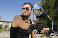 Good looking man holding a motorcycle handle. And blue day sky background Stock Photos