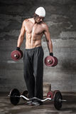 A good looking man lifting weights. On dark background Royalty Free Stock Photography
