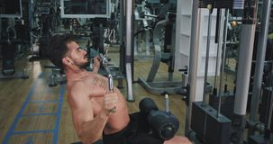 Good looking man with a muscle body at gym working concentrated to developing his abs lifting up the weights. 4k stock video footage