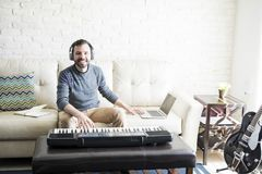 Happy male music composer. Good looking man playing piano and editing music on laptop while sitting at home stock photo