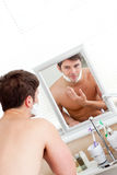 Good-looking man putting shaving foam on his face Stock Images