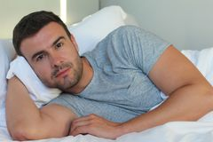 Good looking man smiling in bed.  royalty free stock images