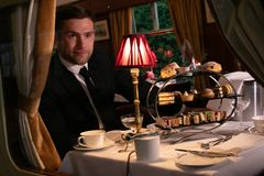 Good looking man in suit enjoying afternoon tea in vintage train carriage stock photos