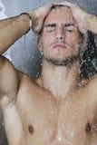 Good looking man under man shower Stock Photos