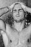 Good looking man under man shower Stock Photo