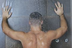 Good looking man under man shower Stock Photography