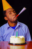 Good looking man wearing blue shirt and hat sitting by table with cake in front, single candle burning, blowing party Stock Images