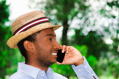 Good looking man wearing blue shirt and summer hat talking on mobile phone while enjoying beautiful day in park Royalty Free Stock Photos