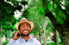 Good looking man wearing blue shirt and summer hat talking on mobile phone while enjoying beautiful day in park Stock Photo