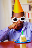 Good looking man wearing blue shirt, white spectacular sunglasses and yellow party hat sitting by table staring at piece. Of cake in front, celebrating alone Royalty Free Stock Photos