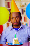 Good looking man wearing blue shirt and yellow party hat sitting by table staring forward, piece of cake placed in front Royalty Free Stock Photos