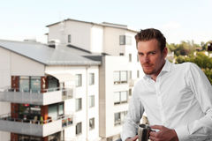 Good looking man in white with coffee mug. Handsome man wearing a white shirt standing on a balcony on a sunny summer day holding a chrome mug Stock Photo