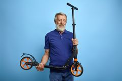 Good looking mature man holding scooter and looking at the camera royalty free stock photos