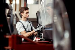 A good-looking mechanic is focused on repairing a light-gray car royalty free stock photography