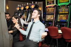 Hitting the jackpot in a slot machine. Good looking men celebrating he just won a lot of money in a slot machine at a casino Stock Photography