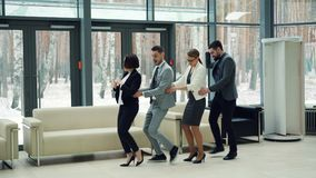 Good-looking men and women business people are dancing in lobby together laughing and having fun at corporate party