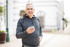 Handsome middle-aged man taking break from workout. Good looking middle-aged man with a mobile phone after morning run in the city Royalty Free Stock Photo