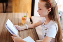 Good-looking modern schoolgirl reading interesting novel. Modern schoolgirl. Good-looking modern schoolgirl feeling really cheerful while reading interesting stock images