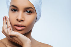 Good looking nice woman applying facial cream. Skin care beauty products. Good looking nice pleasant woman applying facial cream and looking at you while wearing Royalty Free Stock Image