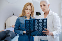 Good looking nice woman listening to the doctors explanation. Worried about husband. Good looking nice pleasant women looking at the X ray photo and listening to Royalty Free Stock Image