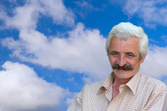 Good looking old man. Closeup Profile on a good looking smiling Old Man and blue sky with clouds in the background Stock Photos